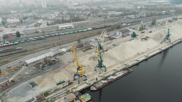 Sand Iron industrial barge with sand floating near cargo working cranes. Sand Extraction