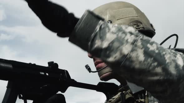 Close up of a soldier firing sub-machine gun, also fixing jammed round.