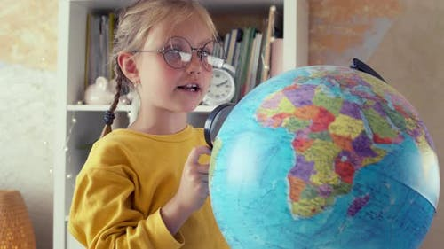 Schoolgirl is Studying the Globe