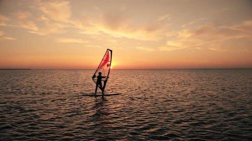 Silhouette of Woman Sailing Windsurf Board Training on Ocean