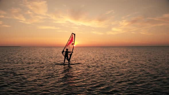 Silhouette of Woman Sailing Windsurf Board Training on Ocean