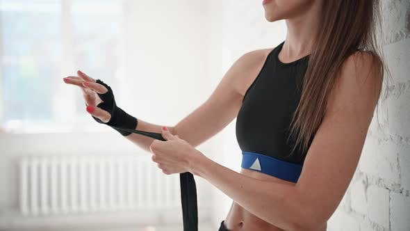 Girl in the Gym Is Wrapping Up Boxing Bandages on Her Hands Before Training a Blow on a Boxing Bag