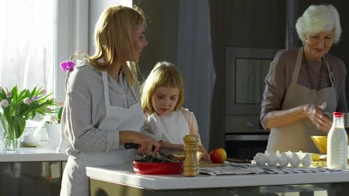 Mother, Daughter and Grandma Cooking Together in Kitchen