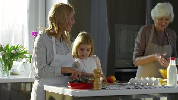 Cover Image for Mother, Daughter and Grandma Cooking Together in Kitchen