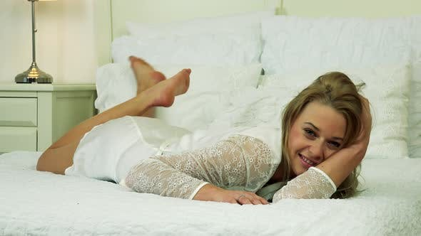 Thumbnail for A Young Woman in White Nightwear Lies on a Bed, Smiles at the Camera and Makes Seductive Poses
