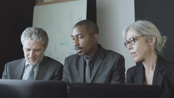 Diverse Coworkers Group Meeting and Talking at Workplace