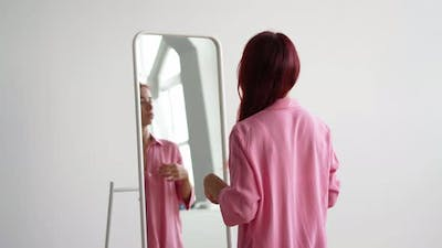 Young Woman in a Pink Shirt Straightens Her Red Hair Near the Mirror