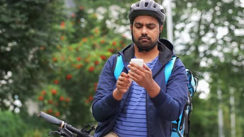 Delivery Man with Bag and Bicycle Calling on Phone