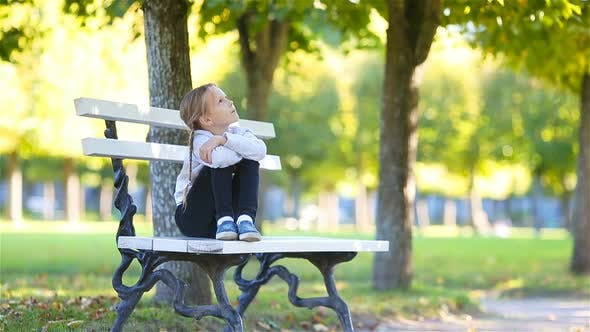 Thumbnail for Adorable Little Girl at Beautiful Autumn Day Outdoors. Cute Kid Sitting on the Bench in Outdoor Park