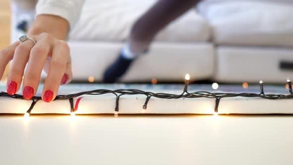 Thumbnail for Macro Girl Hand Aligns Christmas String of Lights on Wall