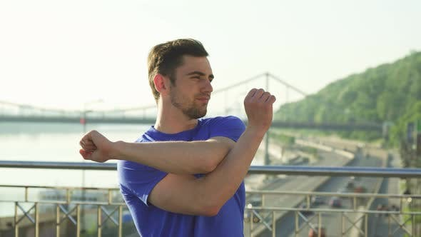 Thumbnail for Handsome Sportsman Stretching His Arms Outdoors Before Working Out