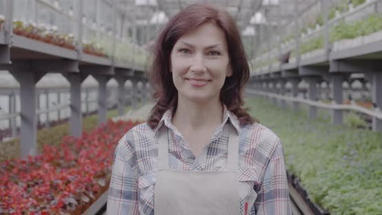 Thumbnail for Portrait of Happy Caucasian Woman Advertising Bottle of Pesticides in Greenhouse. Positive Beautiful