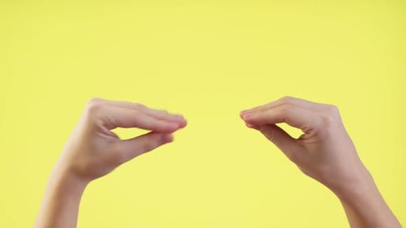 Thumbnail for Woman Showing Talking To Each Other Hands Isolated Over Pastel Yellow Background in Studio