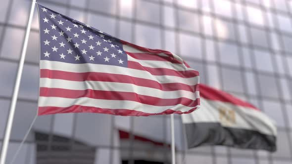 Waving Flags of the USA and Egypt in Front of Modern Skyscraper