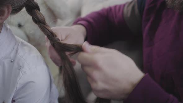Männliche kaukasische Hände Flechten Pigtails. Vater tut Frisur für seine Brünette Tochter. Vaterschaft