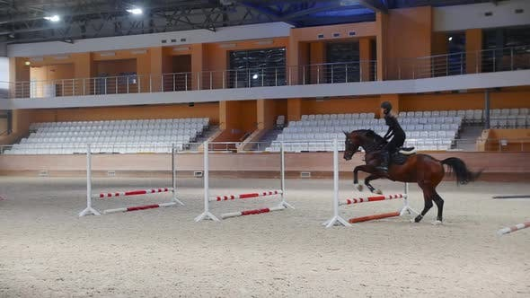 Equestrian Sports  a Woman Jumping Over the Series of Barriers on the Horseback  a Man Passes By