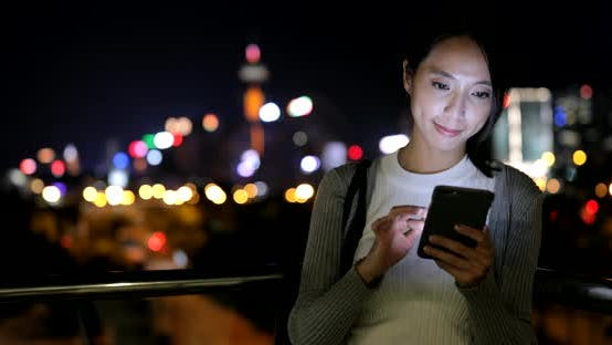 Thumbnail for Woman using cellphone in city at night