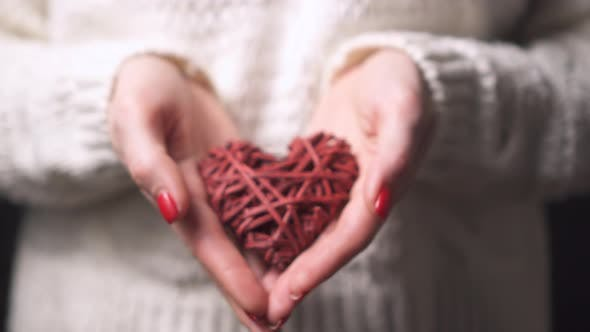 Close-up Female Hands Hold a Decorative Heart, Selective Focus.