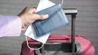 Holding Passport in Hand with Suitcase on Ground