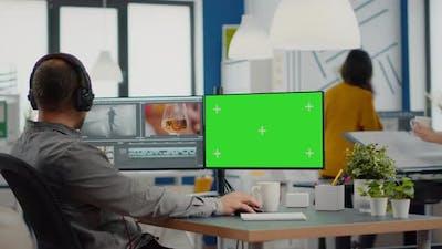 Videographer Using Computer with Chroma Key Display