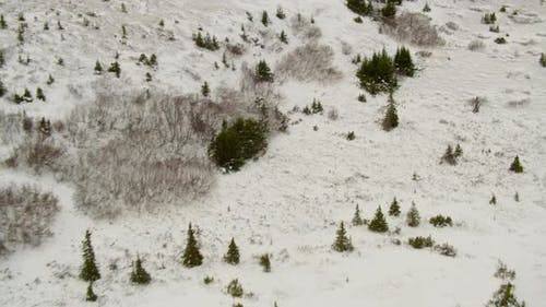 Aerial helicopter shot, land on snowy airstrip in remote airport, snow swirling around, mountain in