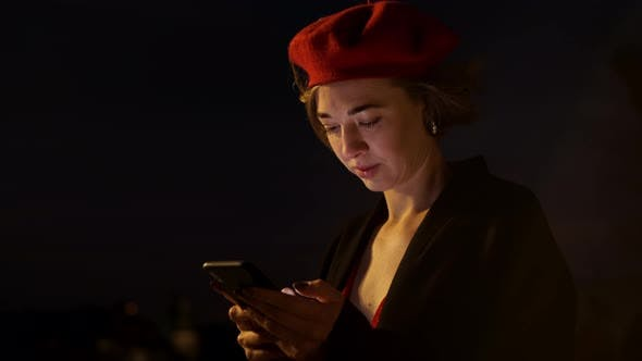 Thumbnail for Twilight. Stylish Young Woman In Red Standing In The Middle Of The Street With Mobile Phone In Her