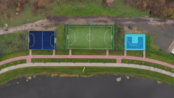 Basketball and football playing fields on city quay along river. Sports recreation zones on quay