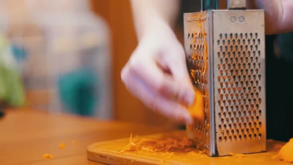 Cover Image for Woman Hands Rubbing Carrots on Grater in a Home Kitchen. Slow Motion