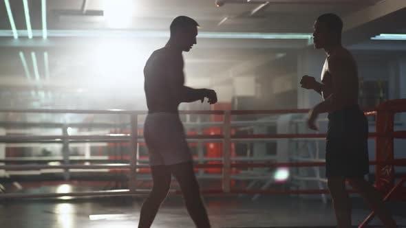 Kickboxen, Mann Boxer trainieren im Sparring, sie führen Streiks mit ihren Füßen und Händen durch, Training