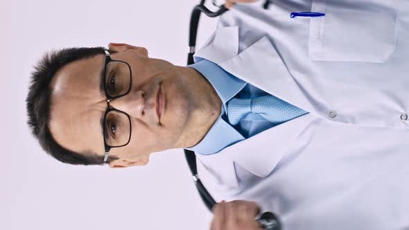 Vertical Shot Middle Aged Doctor Puts a Stethoscope on His Neck Folds His Arms Over His Chest