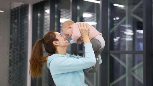 Mother Lifting Baby Above Head in the Airport Having Fun