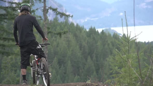 Thumbnail for A mountain biker resting by his bike with a scenic forest in the background