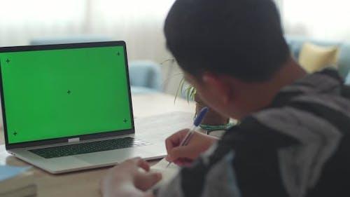 Junge sitzt an seinem Schreibtisch und lernt online auf einem Laptop mit grünem Mock-up-Bildschirm