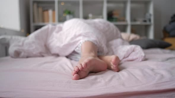 Thumbnail for Closeup View of Feet Lying on Soft White Pillow at Bed