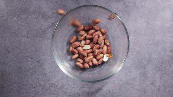 Falling Processed Pea Nuts in a Bowl on Table Top Down