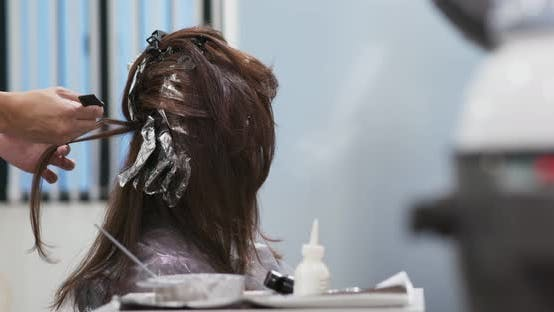 Thumbnail for Hair dresser is dyeing hair of beautiful woman in barber shop