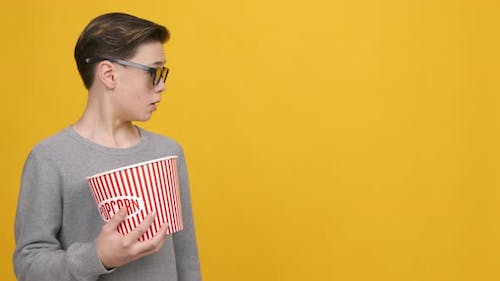 Teen Boy Wearing 3D Glasses Looking Aside Over Yellow Background