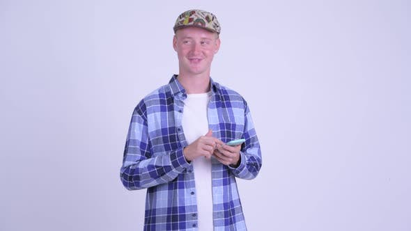 Thumbnail for Happy Young Hipster Man Thinking While Using Phone