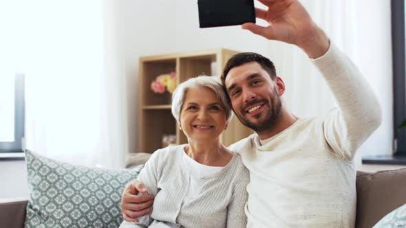 Cover Image for Senior Mother with Adult Son Taking Selfie at Home