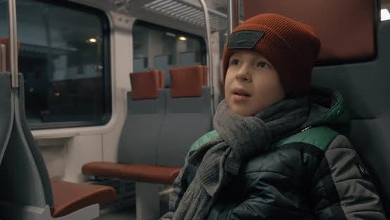 Boy riding on a commuter train