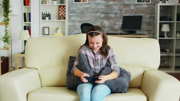 Aufgeregt kleines Mädchen Spielen Video spiele auf ihrem Handy
