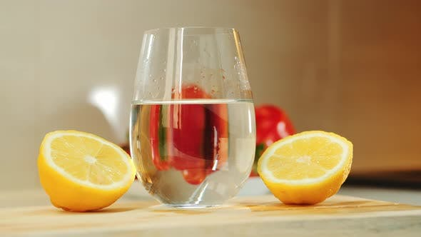 Thumbnail for A Glass with Water Between Two Part of Cut Lemon on Wooden Kitchen Board
