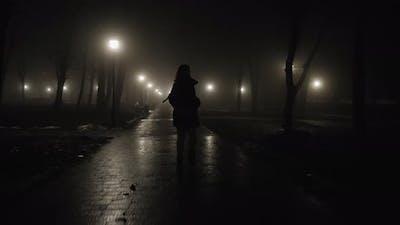 Woman Walking Home at Night Through City Park at Night