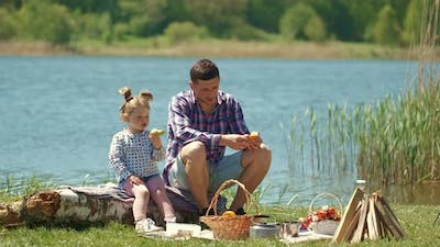 Father with Little Daughter on a Picnic Near the River