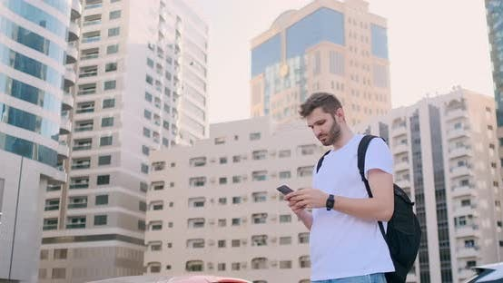 Thumbnail for A Young Man with a Backpack and a Smartphone in His Hands