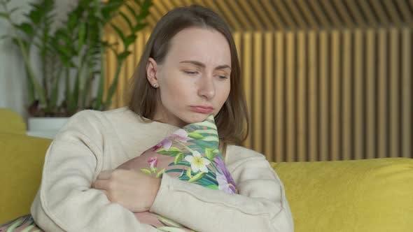 Unglückliche einsame depressive Frau zu Hause sitzt sie auf der gelben Couch