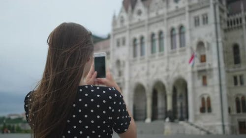 Girl Taking Mobile Photos of Parliament Building in Budapest Hungary