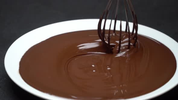 Thumbnail for Macro of Melted Milk or Dark Chocolate Swirl in Plate and Whisk on Concrete Background