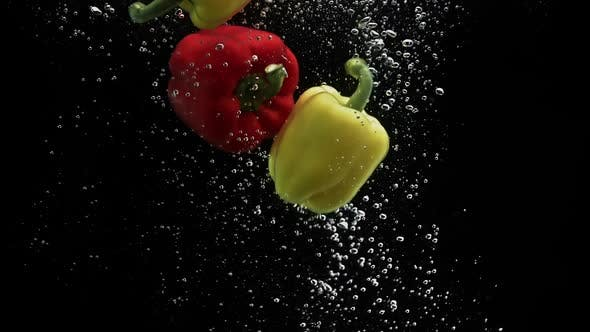Thumbnail for Red and Yellow Peppers Falling in Water and Spinning Air Bubbles on Black Background