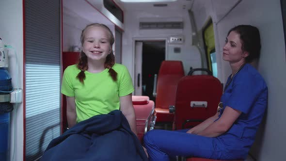 Thumbnail for Nurse with Little Girl Sit in Ambulance Car at Night.